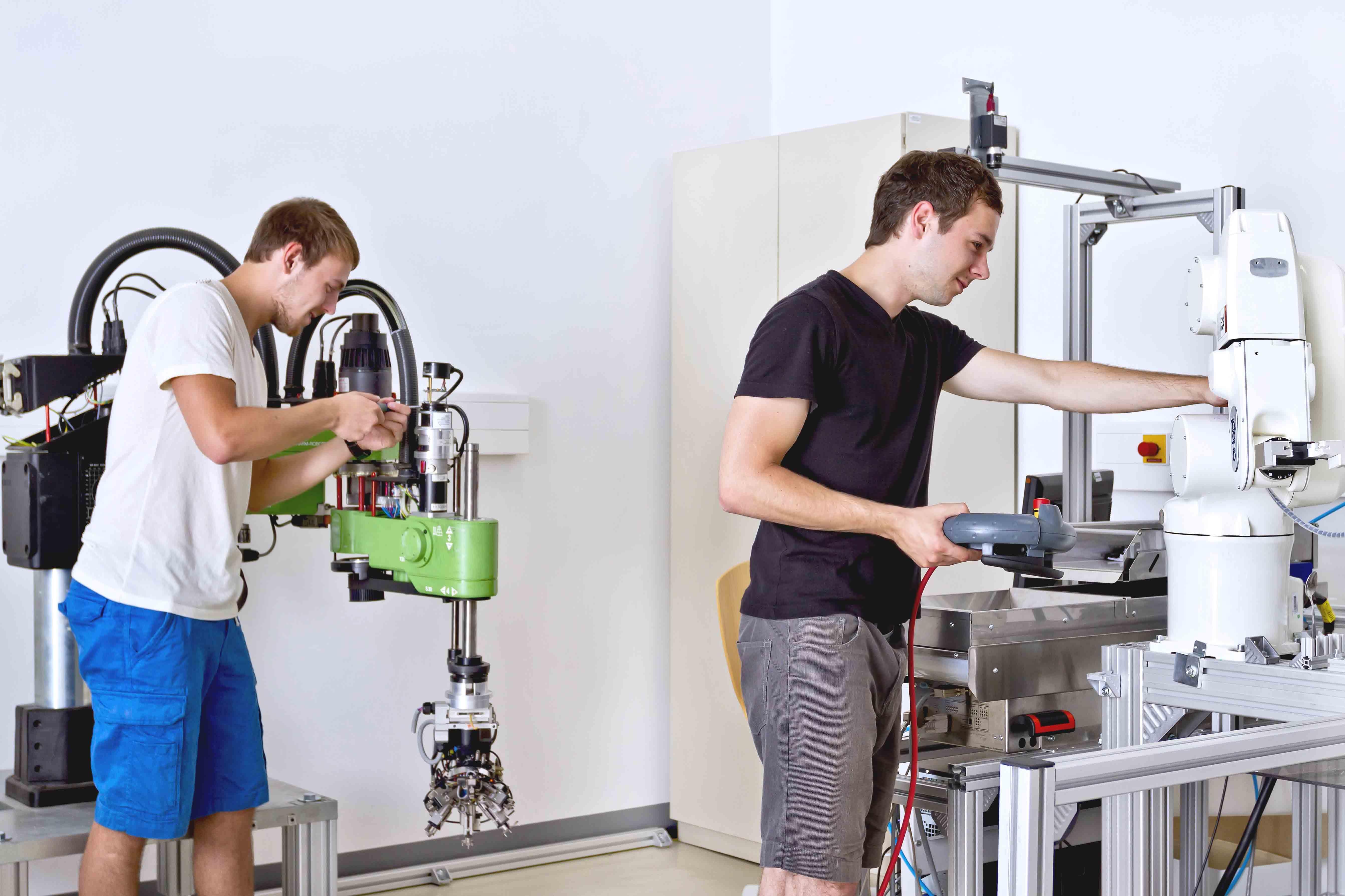 Zwei Studenten, die mit der Bedienung von Robotertechnik beschäftigt sind.